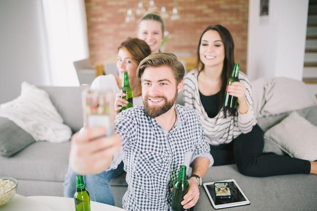 Persone entusiaste con birre che si selfie
