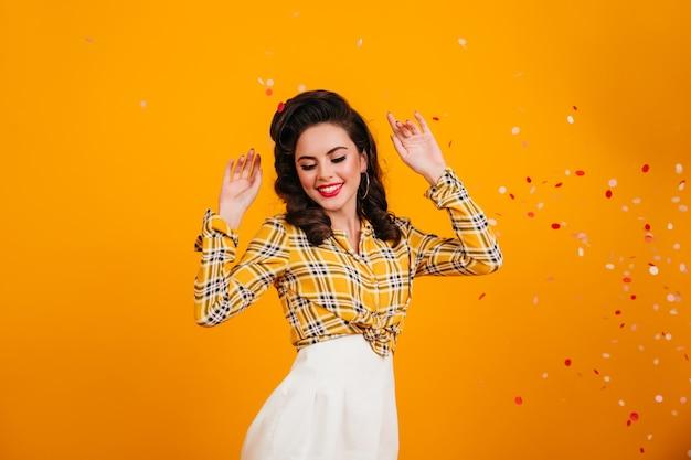 춤과 손을 흔들고 흥분된 핀 업 소녀입니다. 체크 무늬 셔츠에 행복 한 검은 머리 여자의 스튜디오 샷.