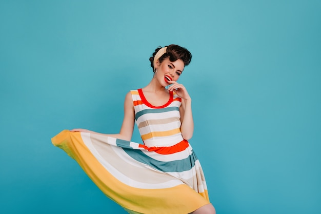 Excited pinup girl playing with striped dress. studio shot of laughing woman dancing on blue background.