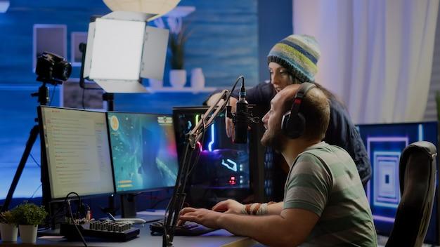 興奮したプレーヤーは、勝利を祝う強力なコンピューターを使用してオンラインビデオゲームの競争に勝ちます。ゲームのトーナメントで実行するrgbキーボードでビデオゲームをプレイするストリーマーゲーマー