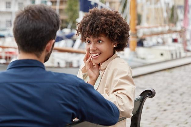 La donna carina dalla pelle scura positiva eccitata ha un sorriso piacevole, pettegolezzi con il migliore amico,