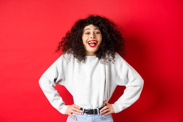 Возбужденная позитивная женщина смеется и улыбается, чувствуя себя оптимистично, глядя на забавный промо, стоящий на красном ба ...