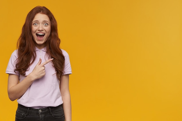 긴 생강 머리를 가진 흥분되고 긍정적 인 여성. 분홍색 티셔츠를 입고. 사람과 감정 개념. 복사 공간에서 오른쪽을 가리키고 주황색 벽 위에 절연