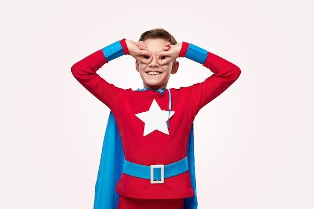 Excited preteen boy in superhero costume doing owl gesture
