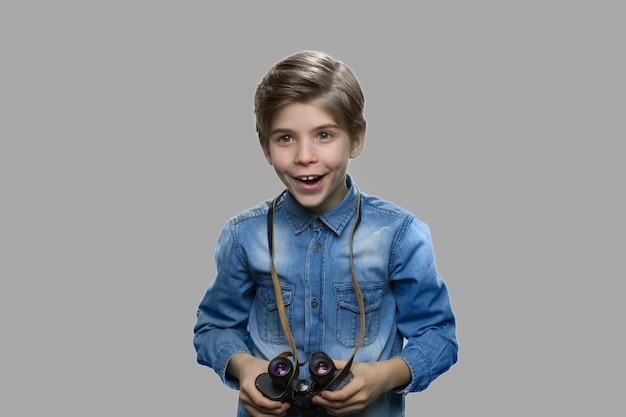 쌍안경을 사용하는 흥분된 초반 소년. 회색 배경에 쌍안경을 들고 데님 옷에 호기심 백인 아이 소년.