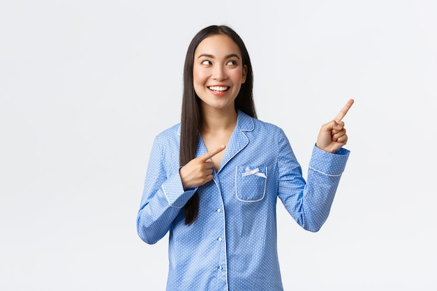 Возбужденная симпатичная азиатская девушка в синей пижаме показывает пальцем в правом верхнем углу и выглядит заинтересованно. довольная женщина в джеме делает выбор, показывая классную рекламу, белый фон