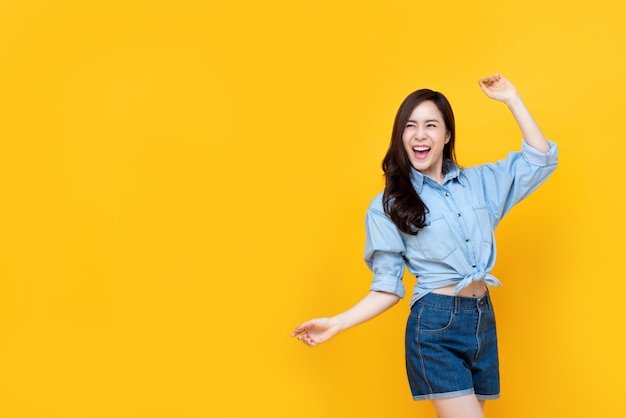 Excited pretty asian woman smiling with arm raise