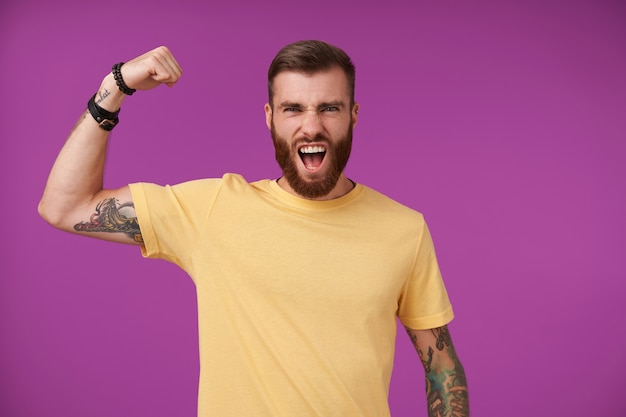 Excited pretty bearded brunette man with tattooes raising his hand and showing power in it, frowning his face with wide mouth opened, posing on purple in yellow t-shirt