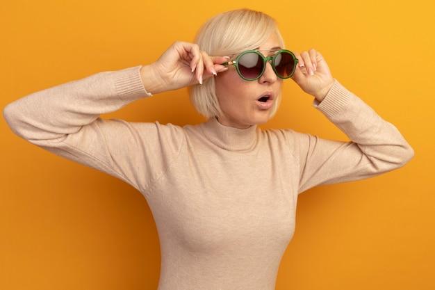 Возбужденная симпатичная славянская блондинка смотрит в сторону через солнцезащитные очки на оранжевом