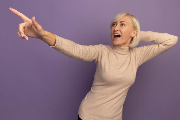 Eccitata bella bionda donna slava mette la mano sulla testa dietro guardando e indicando il lato isolato sul muro viola