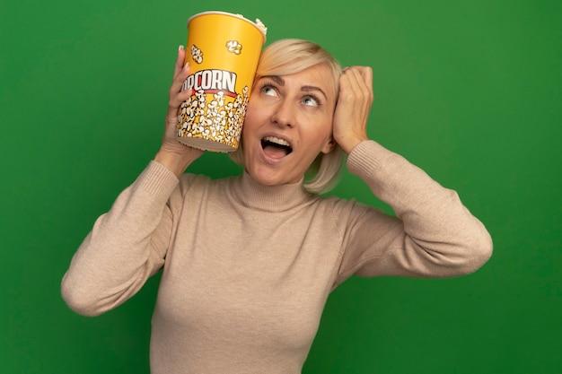 興奮したきれいな金髪のスラブ女性は頭に手を置き、緑の壁に孤立して見上げるポップコーンのバケツを保持します。