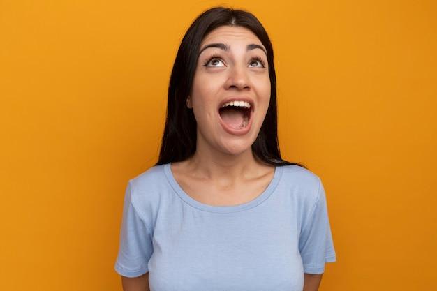 La ragazza caucasica del brunette grazioso emozionante osserva in su sull'arancia
