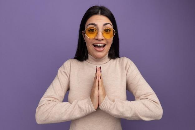 Eccitata ragazza caucasica bella mora in occhiali da sole tiene le mani insieme sulla porpora