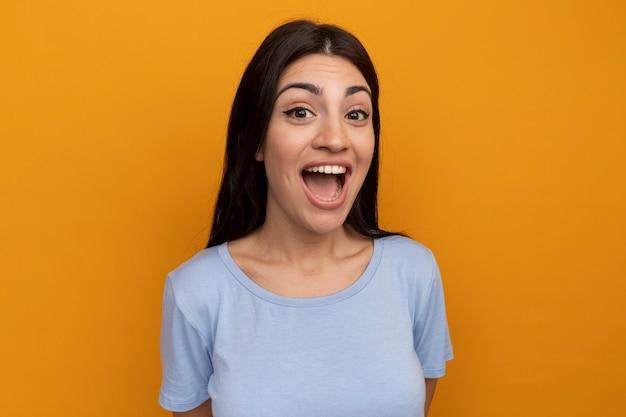 La donna graziosa emozionante del brunette esamina la parte anteriore isolata sulla parete arancione