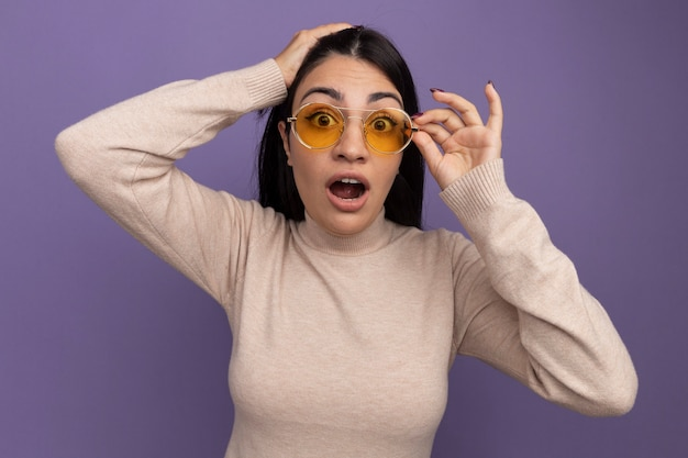 Eccitata bella donna mora in occhiali da sole mette la mano sulla testa e guarda davanti isolato sul muro viola