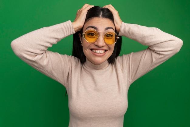 Eccitata bella donna castana in occhiali da sole mette le mani sulla testa isolata sulla parete verde