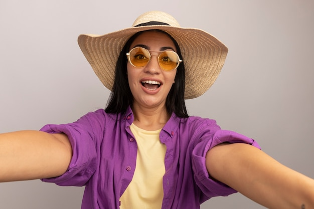 Eccitata bella donna castana in occhiali da sole con cappello da spiaggia finge di tenere la parte anteriore prendendo selfie isolato sul muro bianco