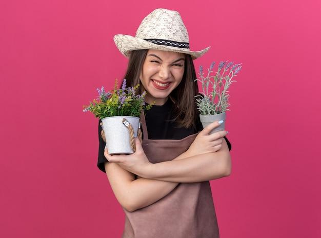 ガーデニングの帽子をかぶった興奮したかなり白人の女性の庭師は、コピースペースでピンクの壁に隔離された植木鉢を保持している腕を組んで立っています