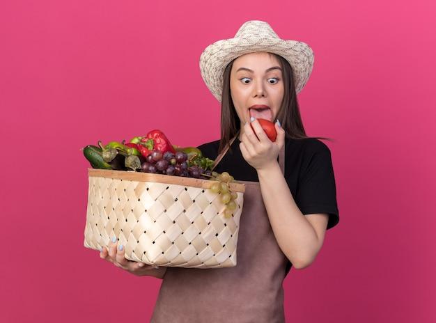 Eccitato giardiniere femmina caucasica che indossa un cappello da giardinaggio sporge la lingua tenendo il cestino di verdure e guardando il pomodoro