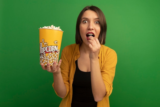 Excited pretty caucasian woman eats and holds bucket of popcorn on green