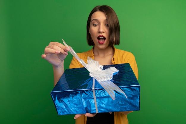 La donna abbastanza caucasica emozionante tiene ed esamina il contenitore di regalo sul verde