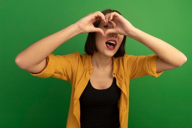 La donna abbastanza caucasica emozionante esamina la macchina fotografica attraverso il segno della mano del cuore sul verde