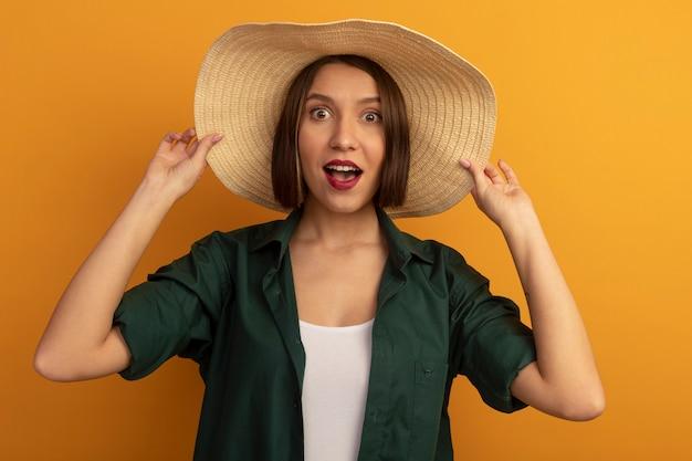 Возбужденная красивая кавказская женщина в пляжной шляпе смотрит в камеру на оранжевом