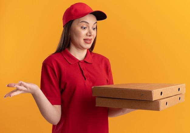 Una donna delle consegne carina eccitata in uniforme tiene e guarda le scatole della pizza