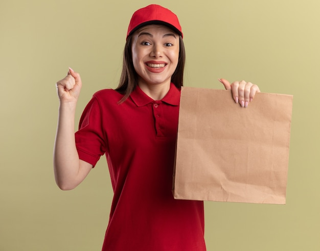 Excited pretty delivery woman in uniform keeps fist and holds paper package isolated on olive green wall with copy space