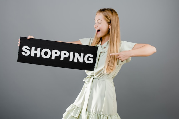 Excited pretty girl pointing finger at shopping sign isolated over grey