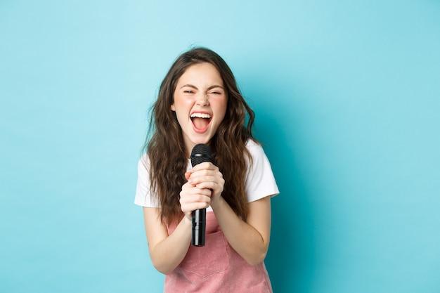 Возбужденная красивая девушка поет караоке, держит микрофон и улыбается счастливым, стоя на синем фоне.