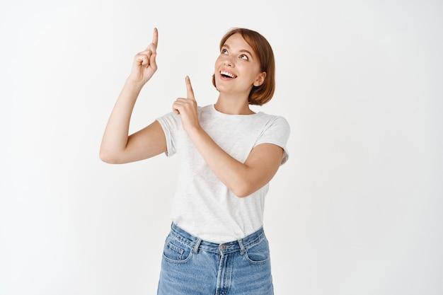 指を上に向けて、笑顔で面白がって、プロモーション広告をチェックして、白い壁に立って、tシャツを着た興奮したきれいな女性