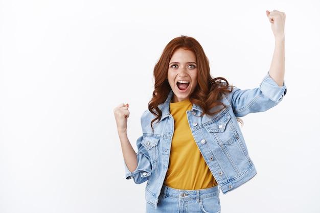 Eccitata bella donna dai capelli rossi in giacca di jeans, alza le mani in sì, evviva il gesto, la pompa del pugno grida incoraggiata, tifa per la squadra preferita, sorride compiaciuta, raggiungi l'obiettivo, celebra il successo