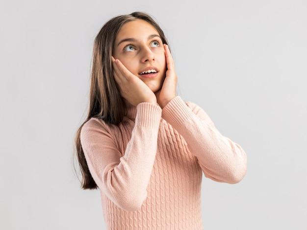 Eccitato bella ragazza adolescente che guarda in alto tenendo le mani sul viso isolato sul muro bianco