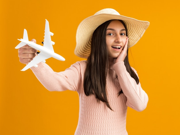 Возбужденная симпатичная девочка-подросток в пляжной шляпе держит модель самолета, делая вау-жест, держа руку на лице, изолированном на оранжевой стене