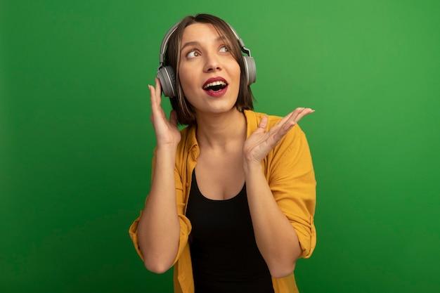 ヘッドフォンで興奮したきれいな女性は、緑の壁に隔離された手で横に見えてポイントします