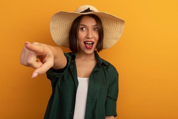オレンジ色の壁に隔離された側にビーチ帽子のルックスとポイントを持つ興奮したきれいな女性