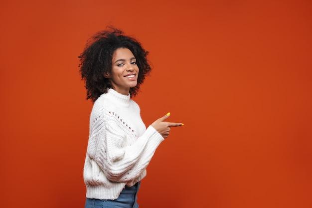 Возбужденная довольно молодая африканская женщина, стоящая изолированно над красной стеной, представляя копию пространства