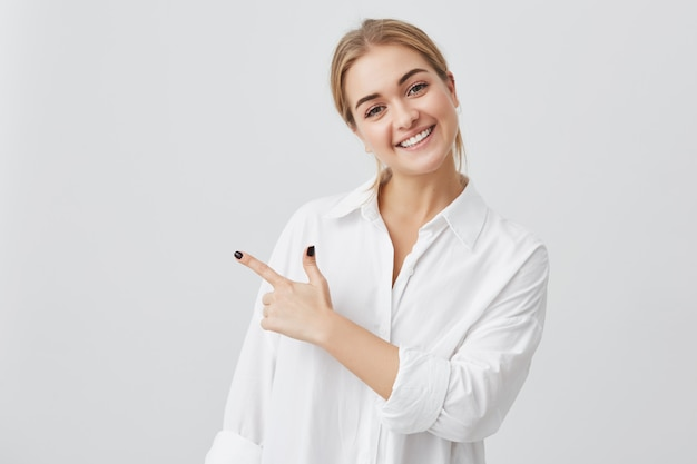 Excited pretty young blonde caucasian woman wearing white shirt pointing her index finger sideways, smiling joyfully with her white teeth, showing something surprising on gray copy space wall