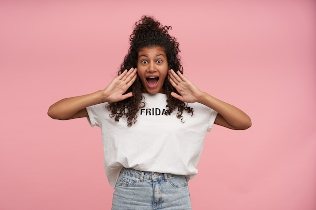 Excited pretty young curly long haired brunette woman with dark skin raising palms to her mouth with wide eyes and mouth opened, isolated on pink