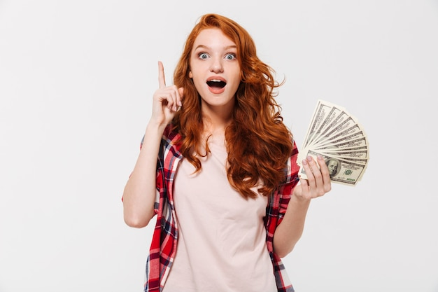 돈을 들고 흥분된 꽤 젊은 빨강 머리 아가씨는 아이디어가 있습니다.