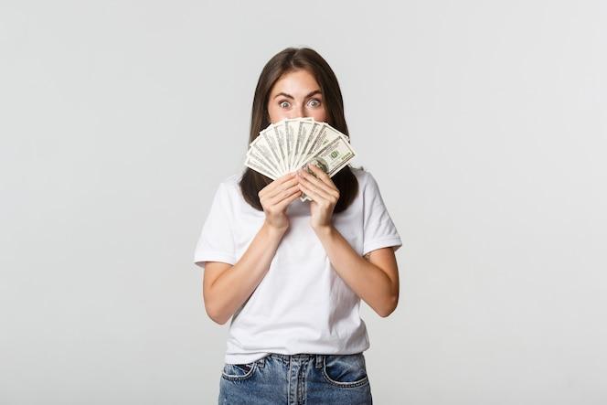 Возбужденная красивая молодая женщина, держащая деньги на лице, стоя белая.