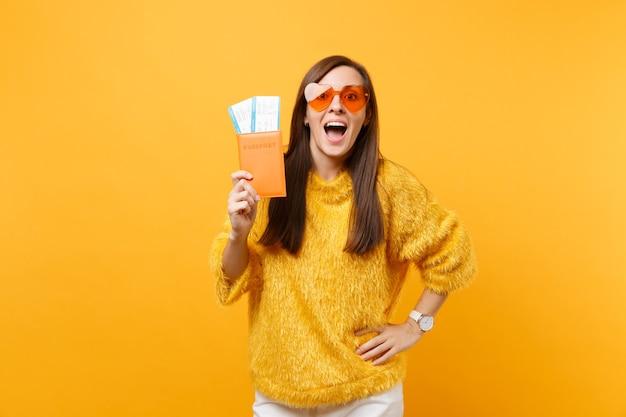 모피 스웨터를 입은 흥분한 예쁜 젊은 여성, 여권을 들고 있는 주황색 하트 안경, 밝은 노란색 배경에 격리된 탑승권. 사람들은 진실한 감정, 라이프 스타일. 광고 영역입니다.