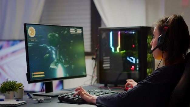 챔피언십 우승을 축하하는 흥분된 프로 e스포츠 게이머, 우주 슈팅 게임에서 우승한 여성. 강력한 rgb 컴퓨터를 이용한 프로 사이버 게임 온라인 토너먼트 라이브 스트리밍 챔피언십