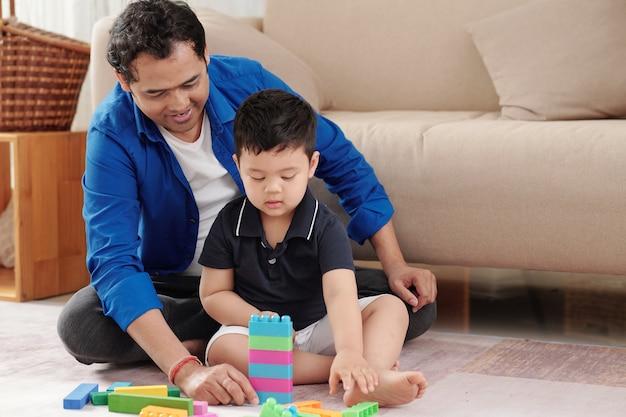 장난감 블록으로 타워를 짓는 어린 아들을 보고 있는 자랑스러운 아버지