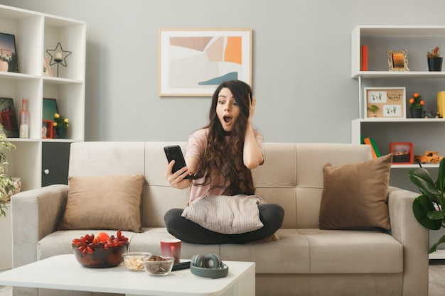 Взволнованная, положив руку на голову, молодая девушка держит и смотрит в телефон, сидя на диване за журнальным столиком в гостиной