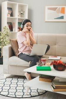 リビングルームのコーヒーテーブルの後ろのソファに座っているヘッドフォンを身に着けているラップトップで口に手を置く興奮