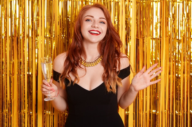 Excited red haired female with spreading hands aside, holding glass of wine, celebrating new year, standing against yellow wall with golden glitter.