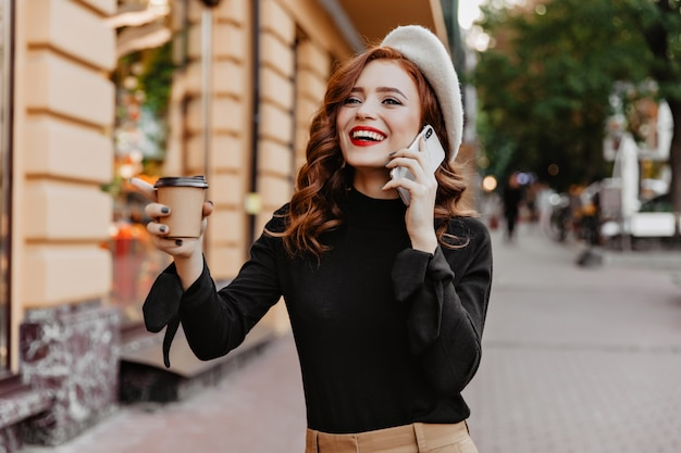 Excited red-haired girl drinking coffee on the street. appealing stylish woman talking on phone on city wall.