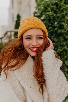 冬にポーズをとるニット帽の興奮した赤毛の女性。屋外で笑顔のコートを着たロマンチックな生姜の女性。